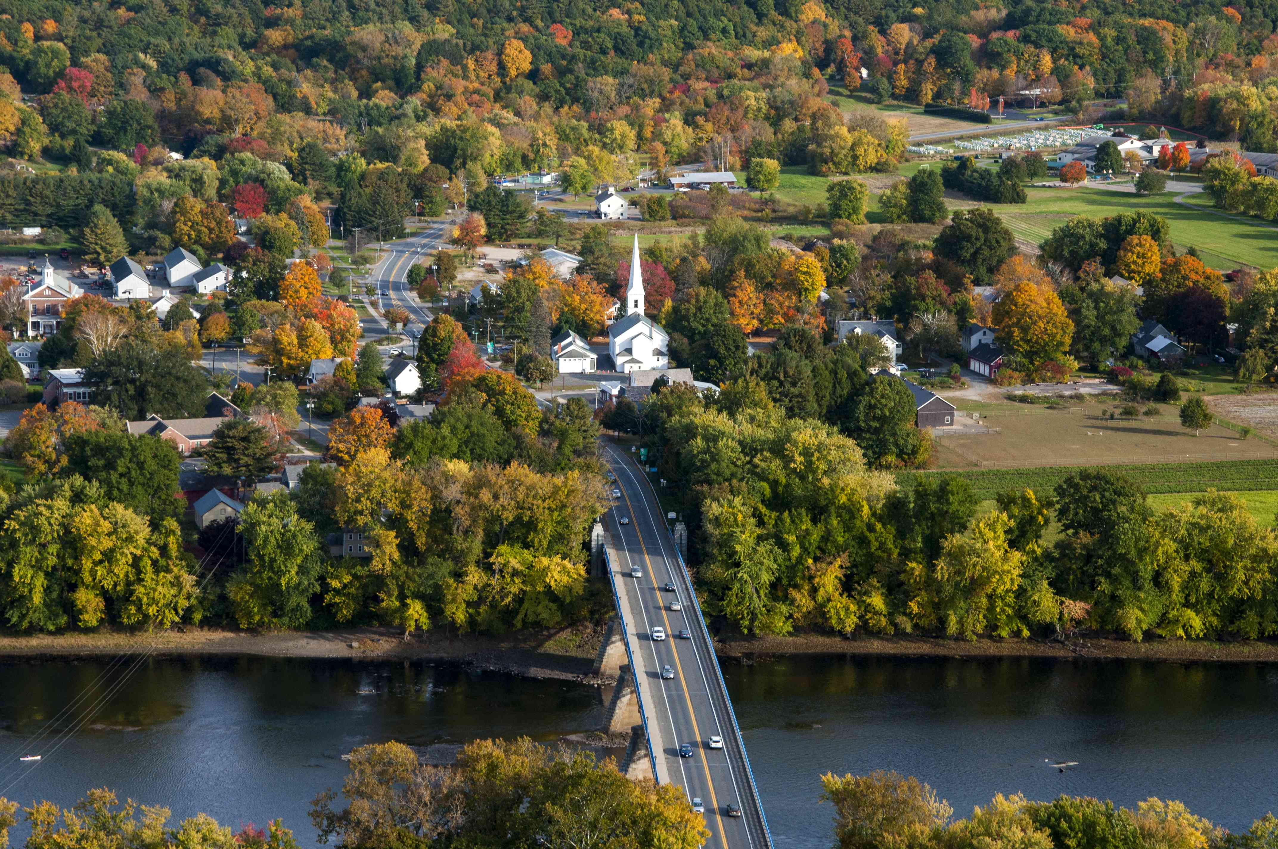 view of small massachusetts town and highway going over a river with some orange and red trees