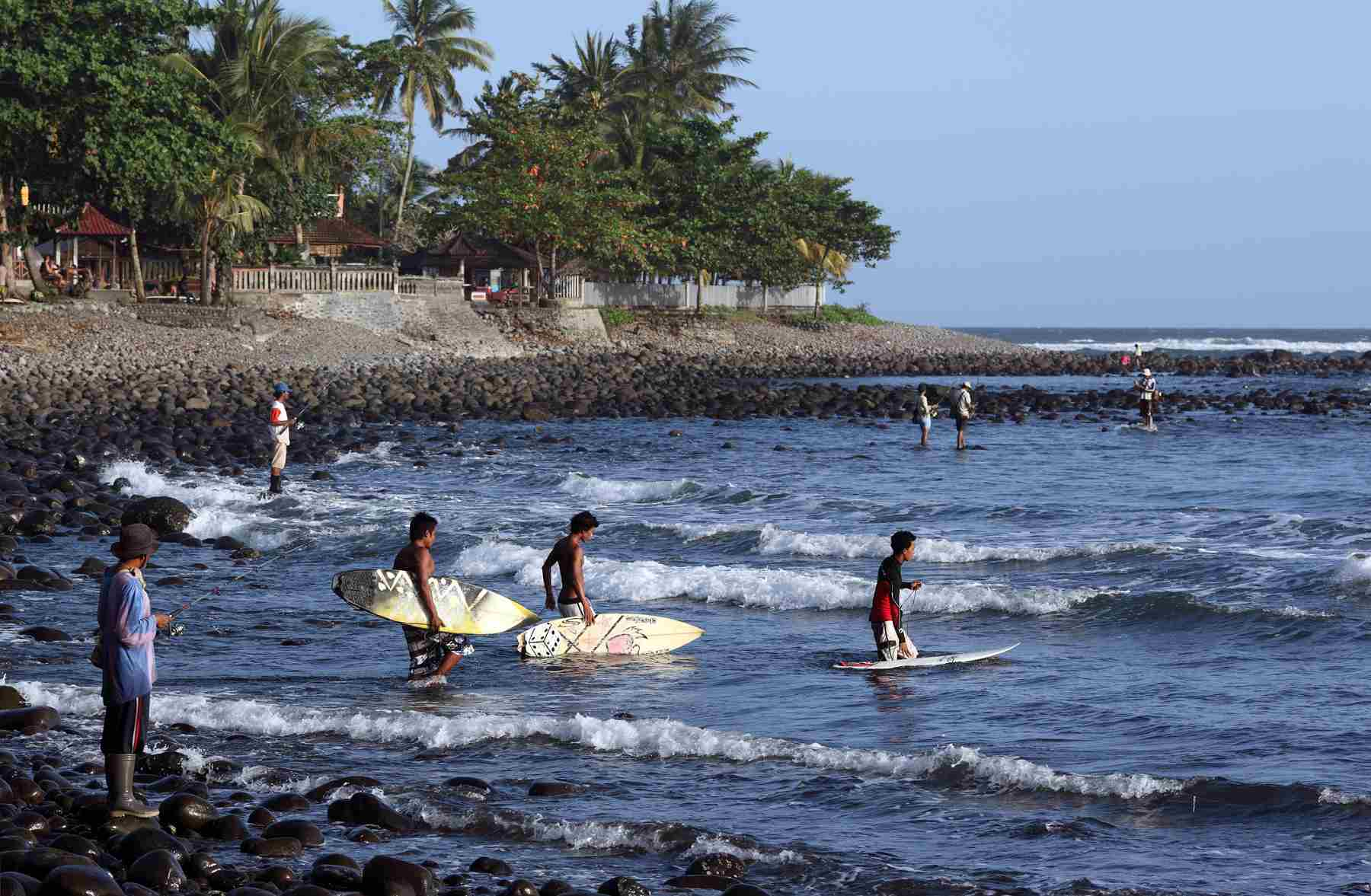 Local surfers head out to catch Medewi Beach's waves.