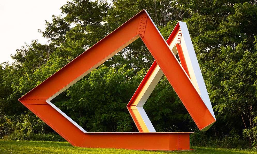 Angular orange metal sculpture with trees behind it