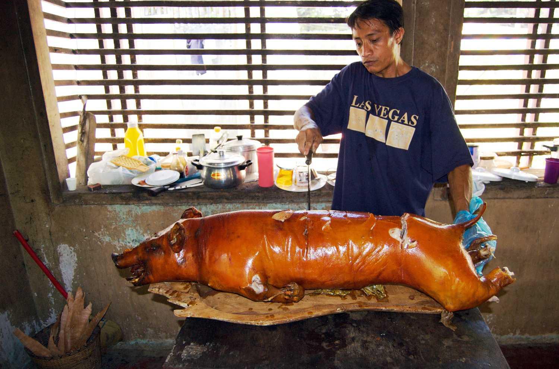 Un hombre tallado un cerdo asado