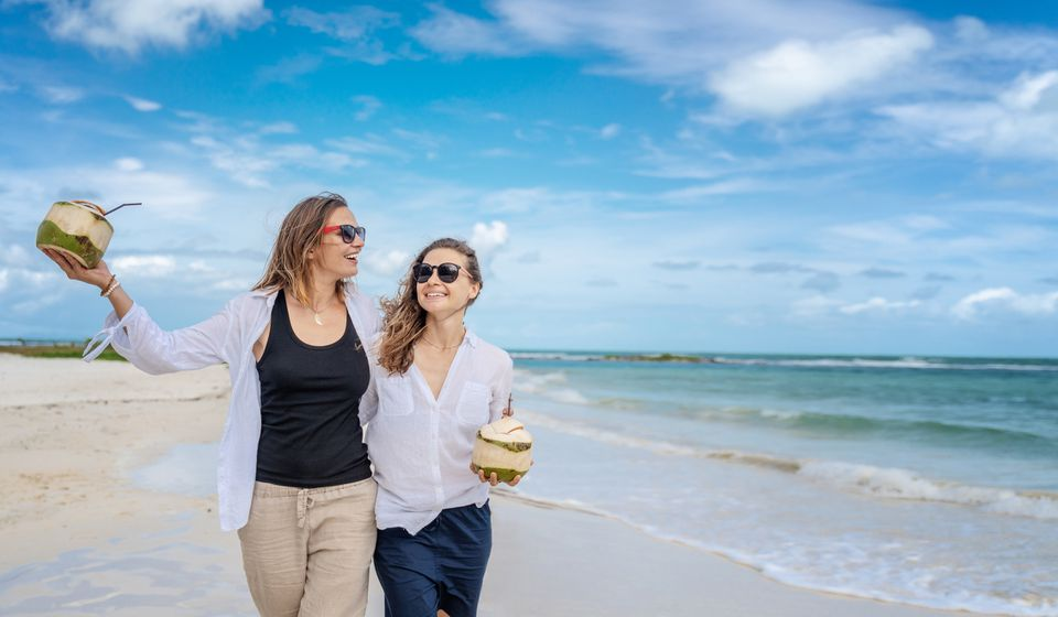 Beautiful young lesbian couple with white shirts with fresh coconuts in their hands walks on a tropical paradise beach, wedding, honeymoon, travel, vacation concept