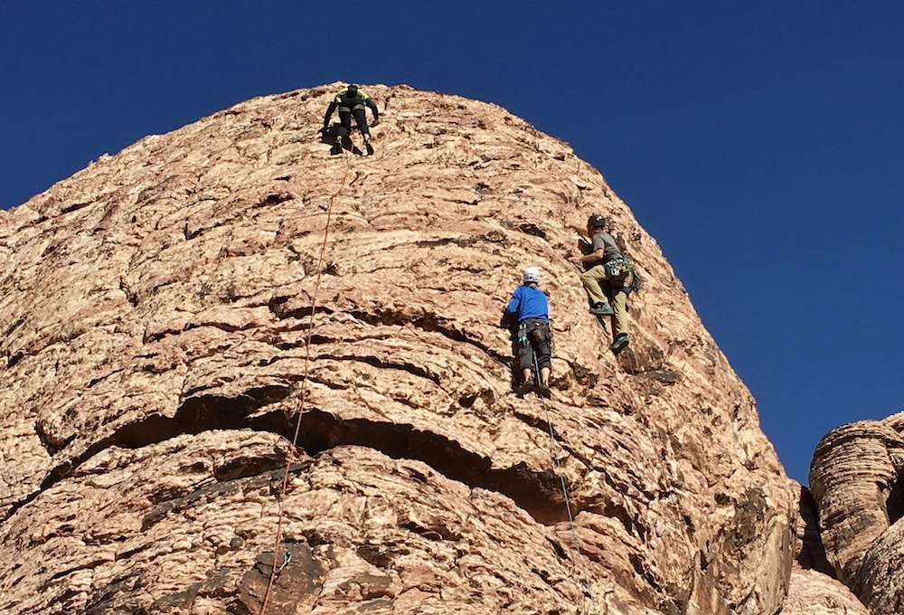 Three climbers going up a sandstone rock wall.