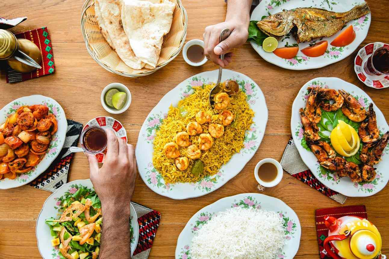 two different hands reaching over a table with many plates of middle eastern food like rice and roasted shrimp