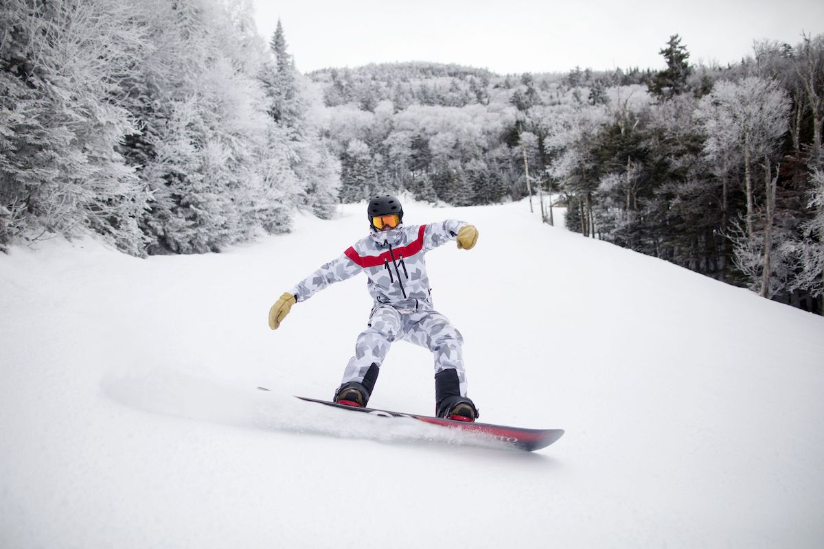 A snowboarder carves through fresh snow with a forest in the background.