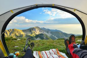Tent view of mountain range with hiking boot in the foreground