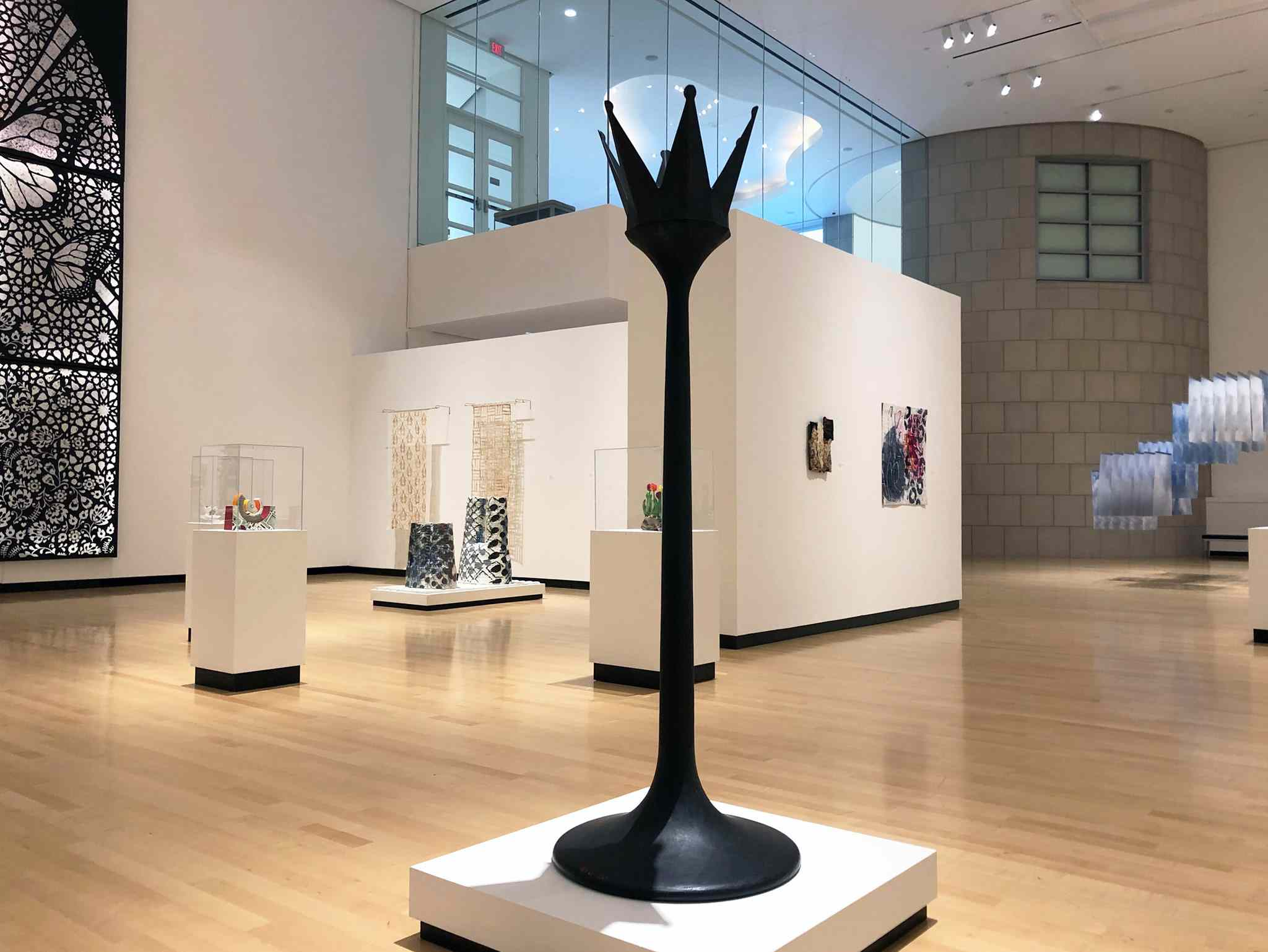 Black sculpture in the center of a large art gallery room