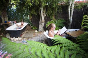 Backpackers at The Barn hostel relax in a unique old fashioned outdoor bathtub after a long day of hiking through the Abel Tasman National Park in New Zealand