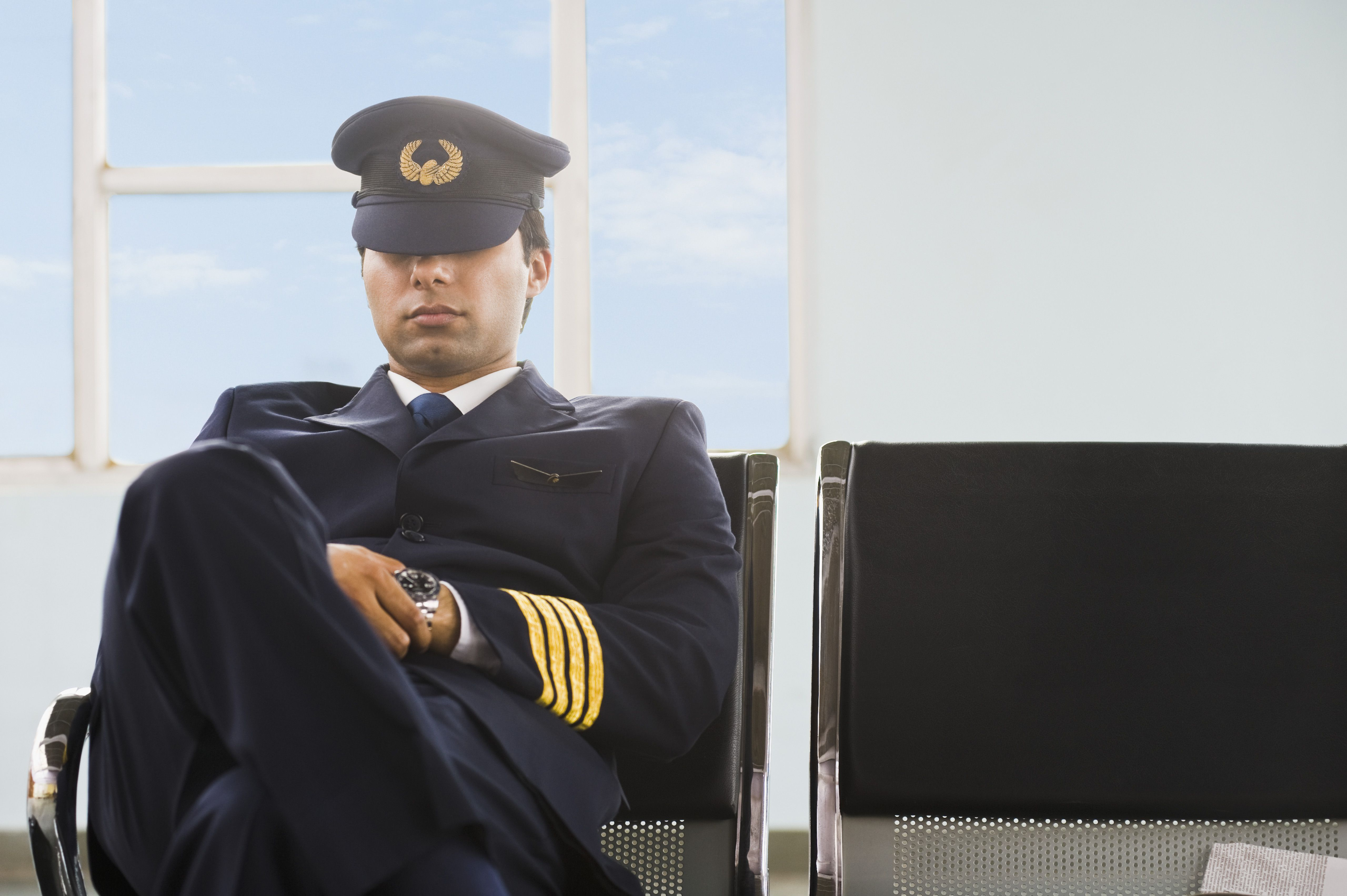 Pilot napping on the bench at an airport