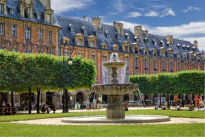 The Fountain and green trees at Place des Vosges in Paris