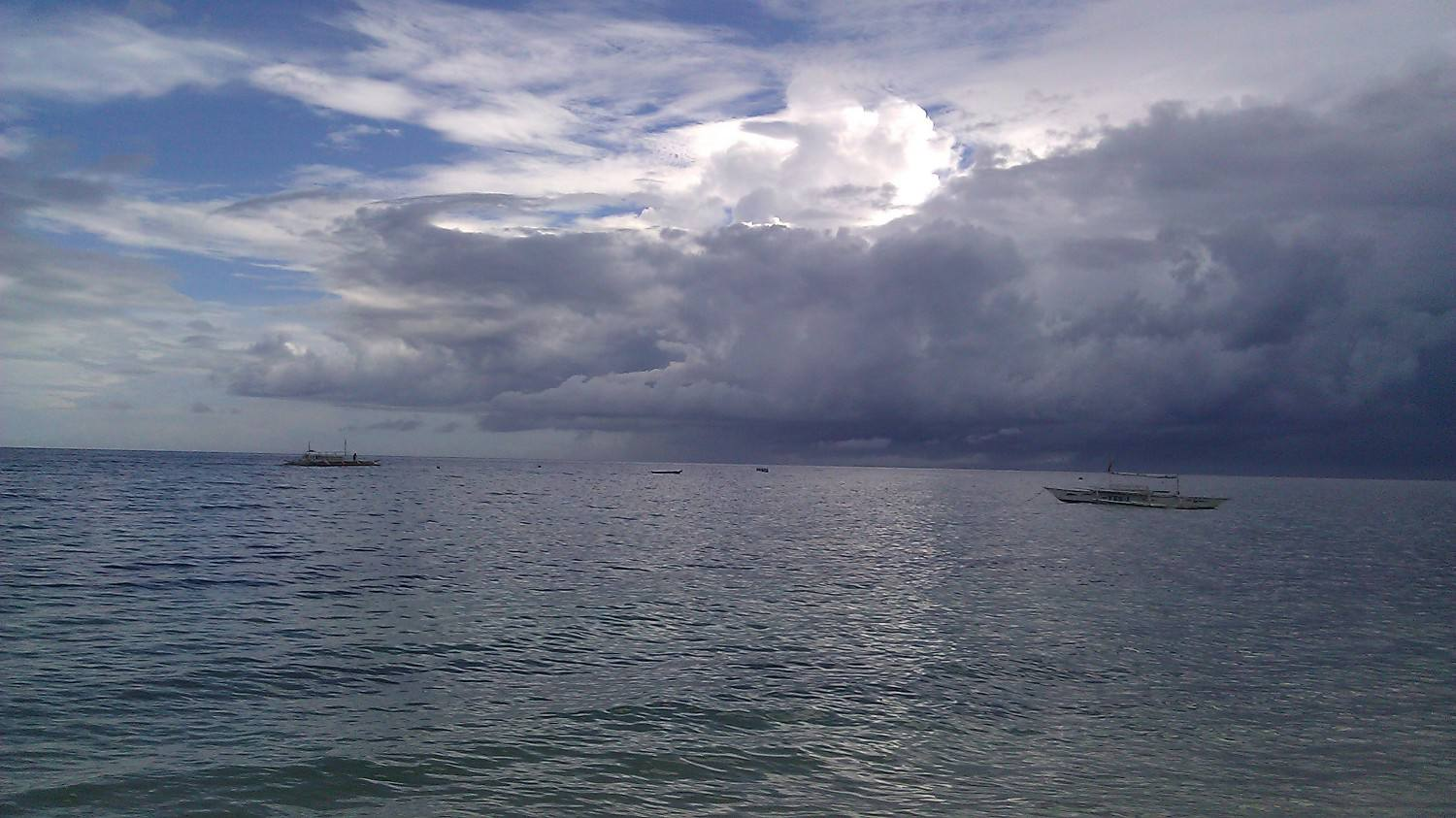 Stormy clouds above a small boat at sea