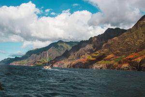 Sailboat sailing down the Napali Coast line