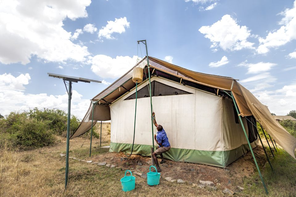 Camp guide preparing a bucket shower outside a safari tent in Kenya