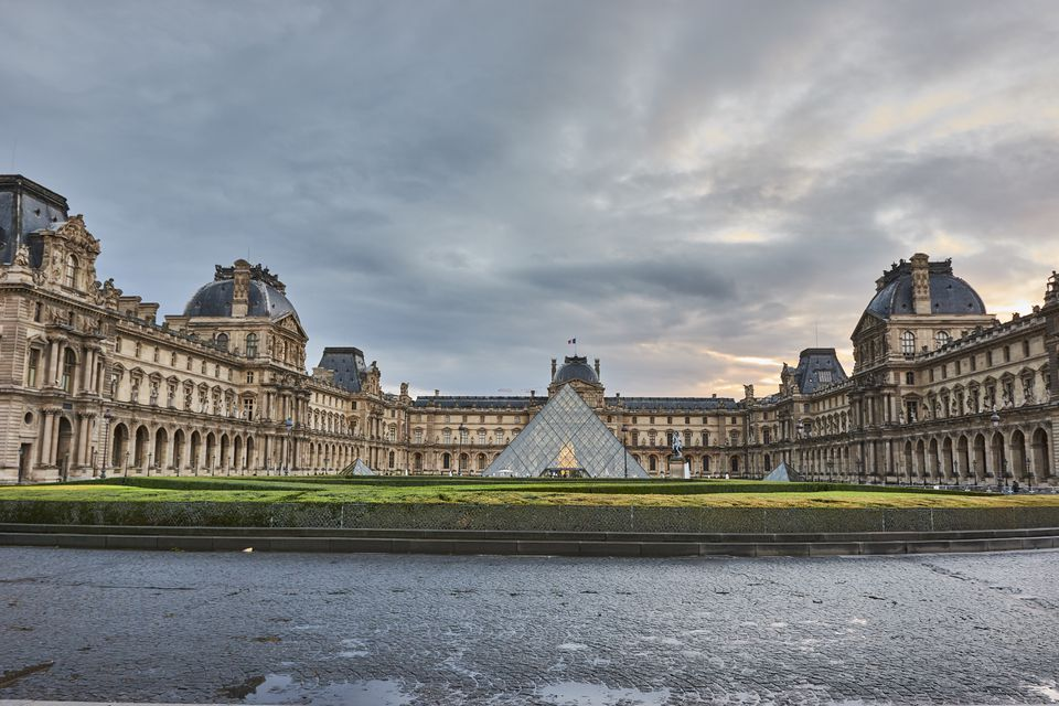 Exterior view of the Louvre Museum with the pyramid in front.