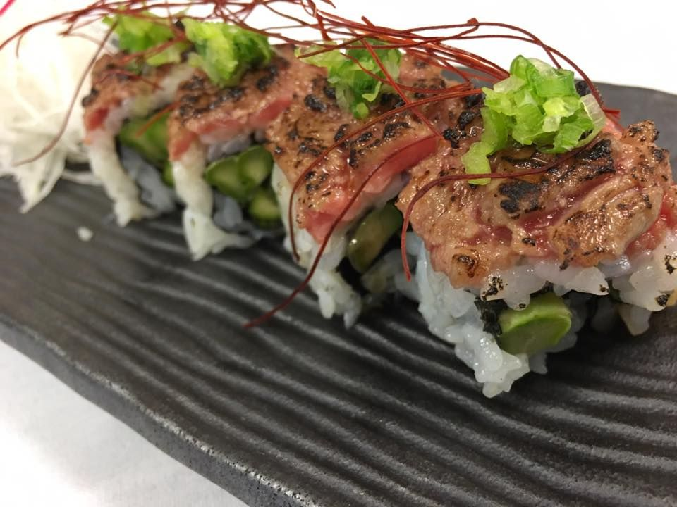 Rollo de sushi de res Wagyu con espárragos, cebolletas y chile rallado