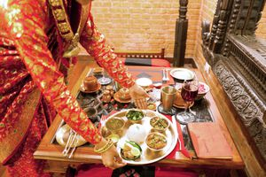 woman reaching down to place a platter of food onto a low table