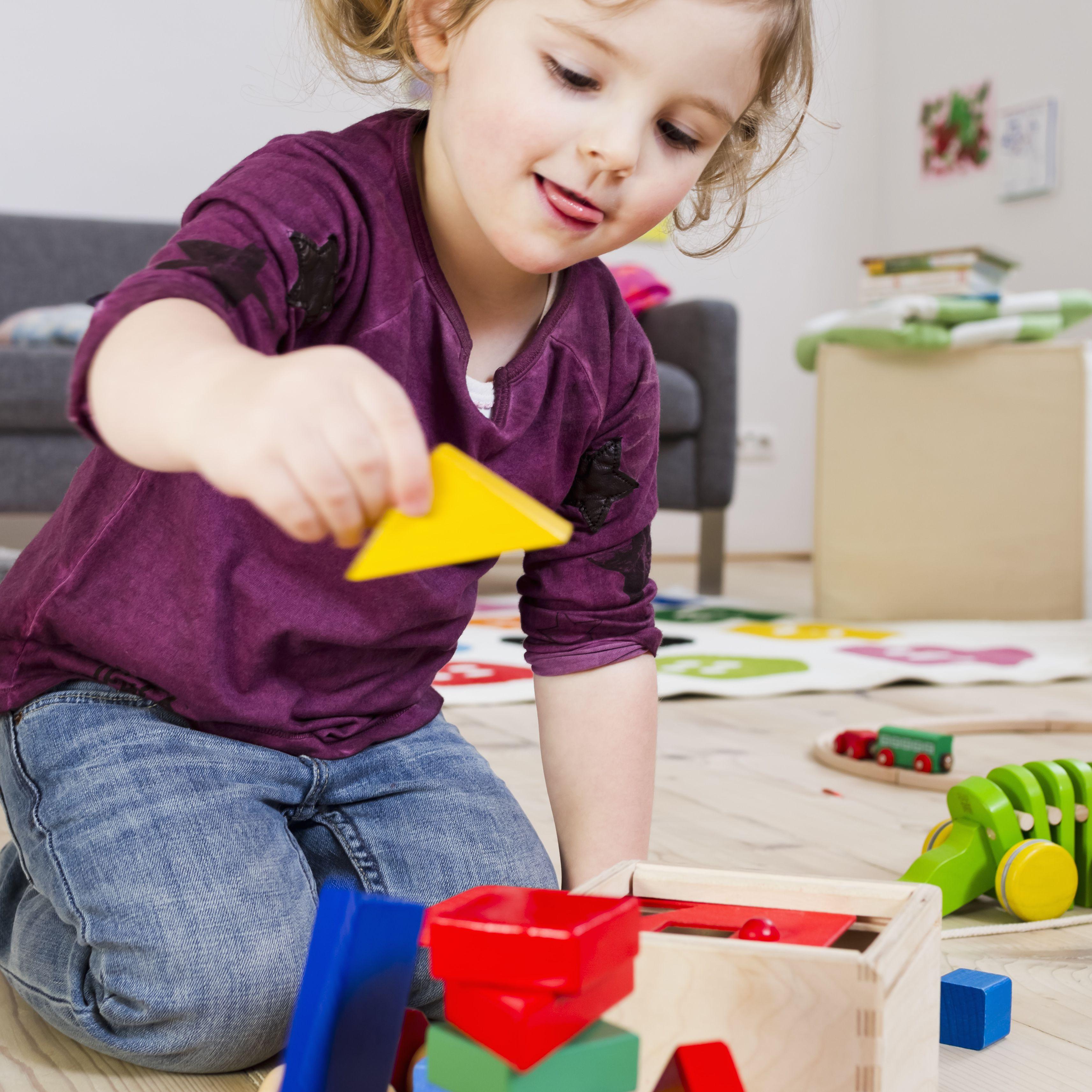 Niña pequeña hace una torre con bloques