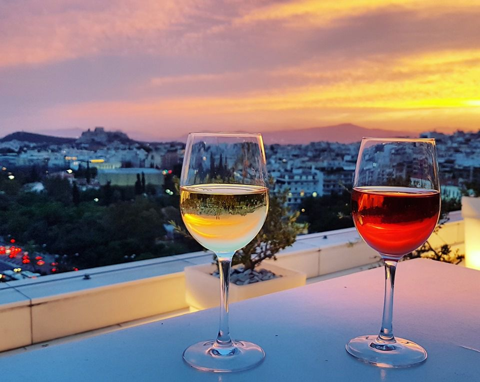Glass of red wine and glass of white wine on a table with views of Athens at sunset at the Galaxy Bar in Athens