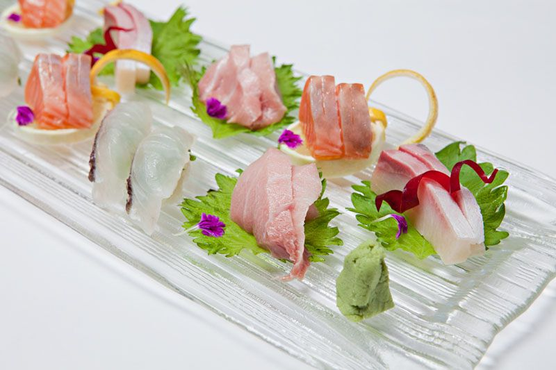 Assorted sashimi pairs on a clear, glass plate with wasabi and small purple flowers for garnish