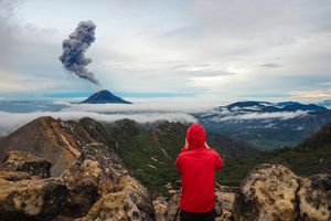A person hiking in Sumatra watches an active volcano