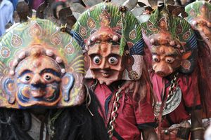 people wearing colorful traditional masks with prominent eyes as part of a festival