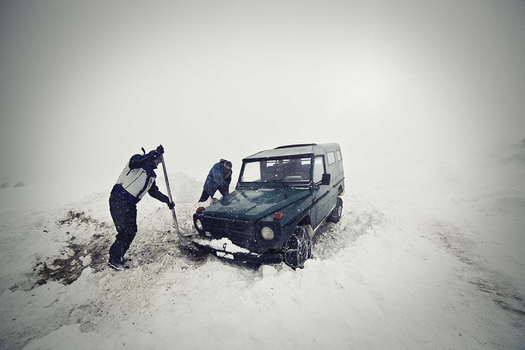 Hombres quitando la nieve con una pala en automóvil