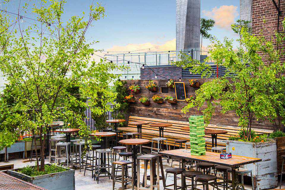 Outdoor par with trees and tall tables. There is a green jumbo jenga game of a rectangular table