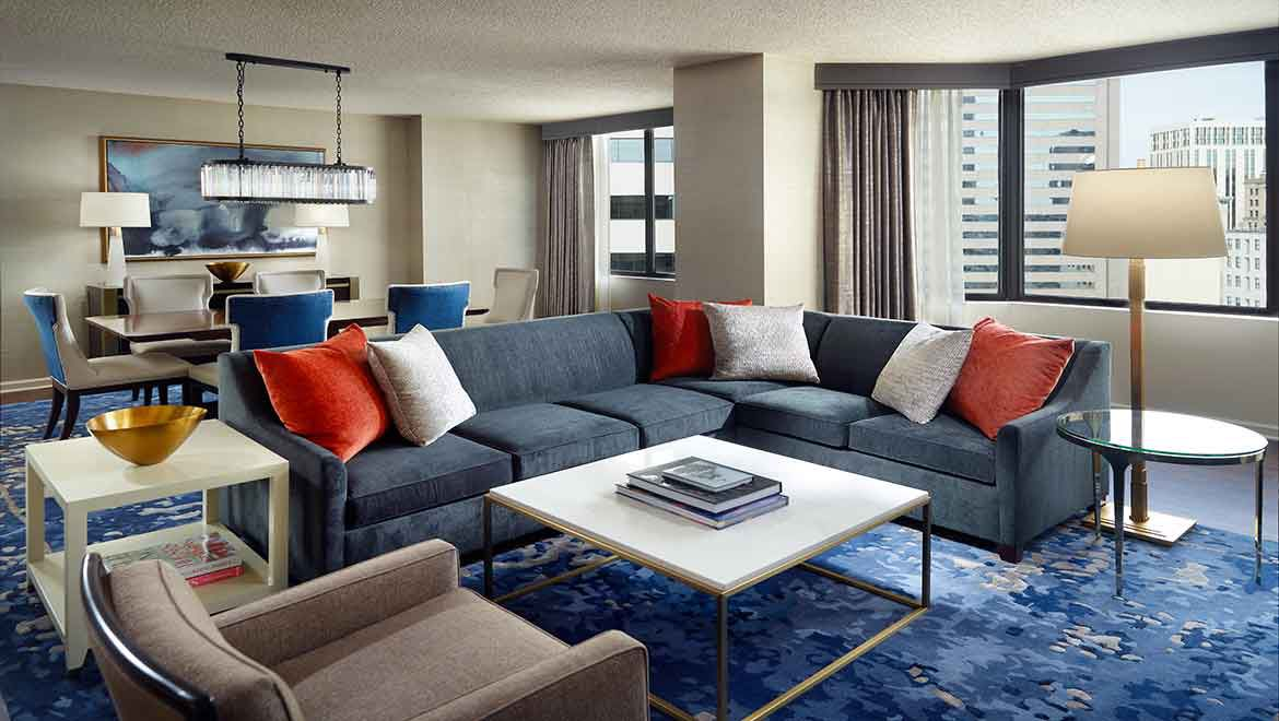 Hotel suite with a large blue sectional with a dining table behind it