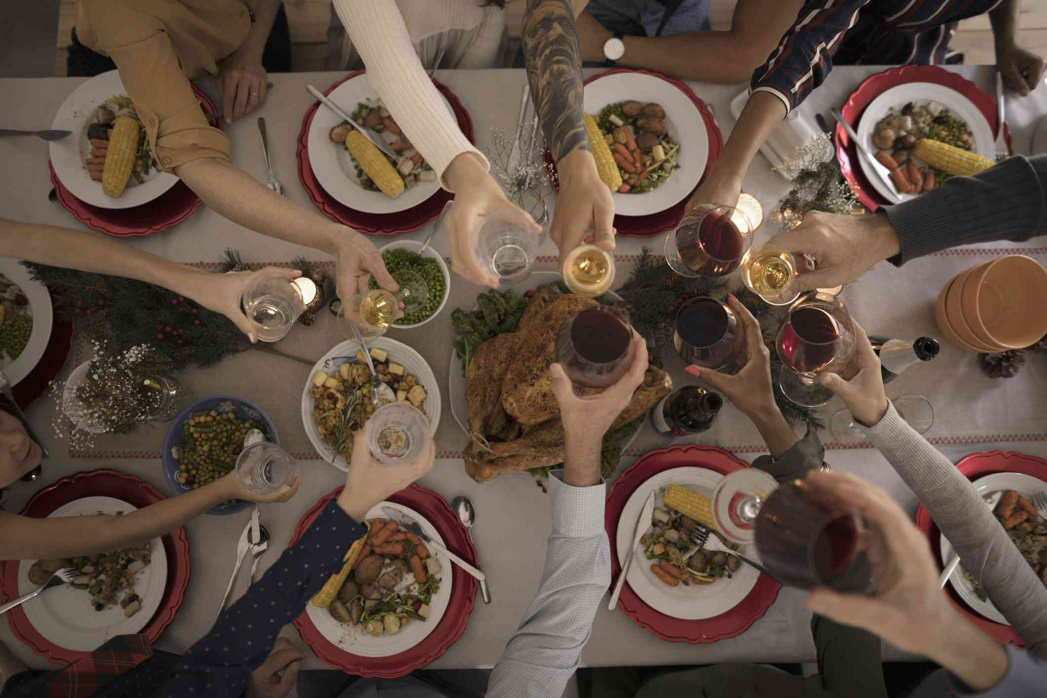 People toasting glasses over a turkey dinner for Canadian Thanksgiving