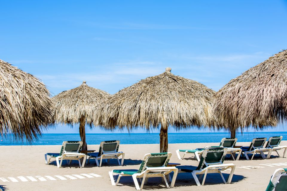 Lounge Chairs And Thatch Umbrellas On Tropical Beach