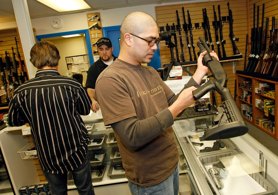 Man holding a rifle as gun store owner looks on