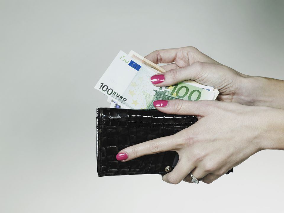 Woman taking euros from her wallet
