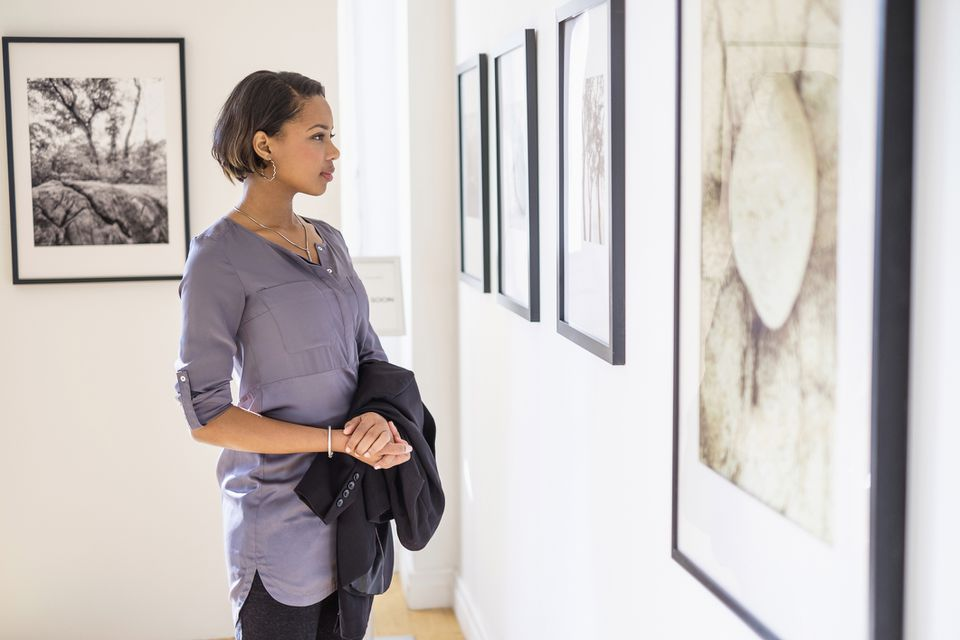 Woman admiring photographs in a contemporary art gallery