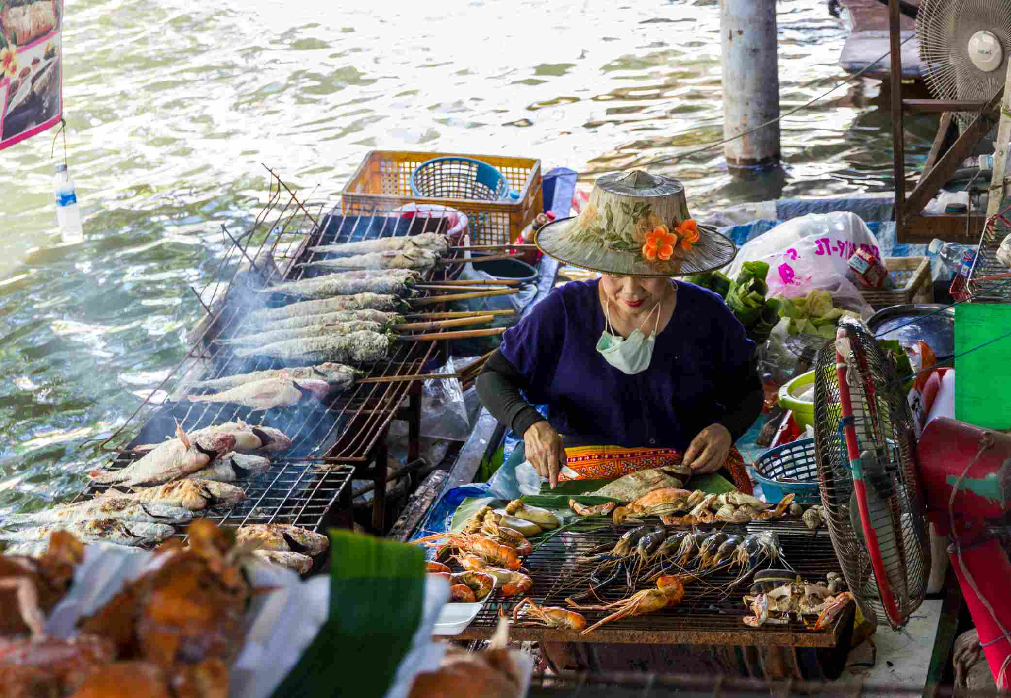 Thai woman grills sea food in a boat at Taling Chan Floating Market