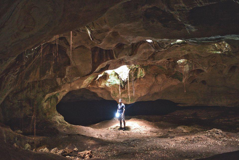 Un hombre explora una cámara subterránea en una cueva en Cuba.
