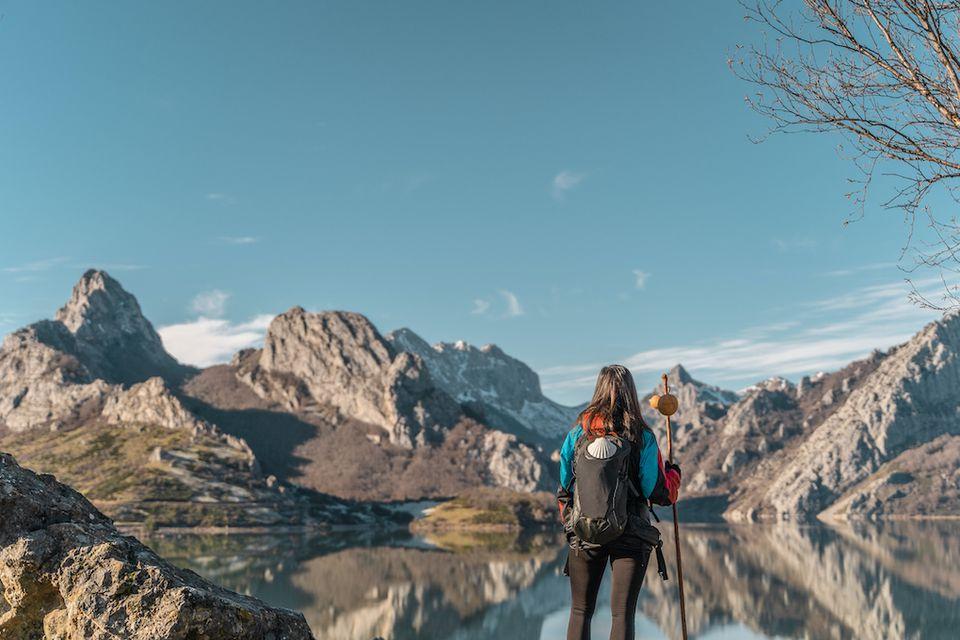 Una excursionista femenina se para frente a un lago espejo y acantilados rocosos