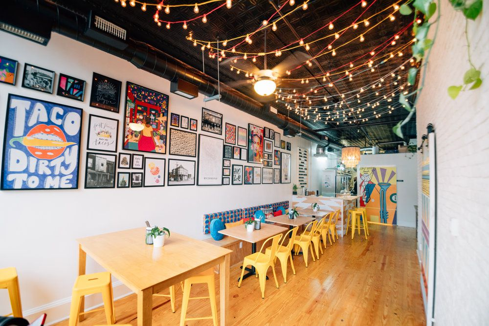Airy and small restuarant dining room with a variety of posters and photographs on the wall and string lights on the ceiling