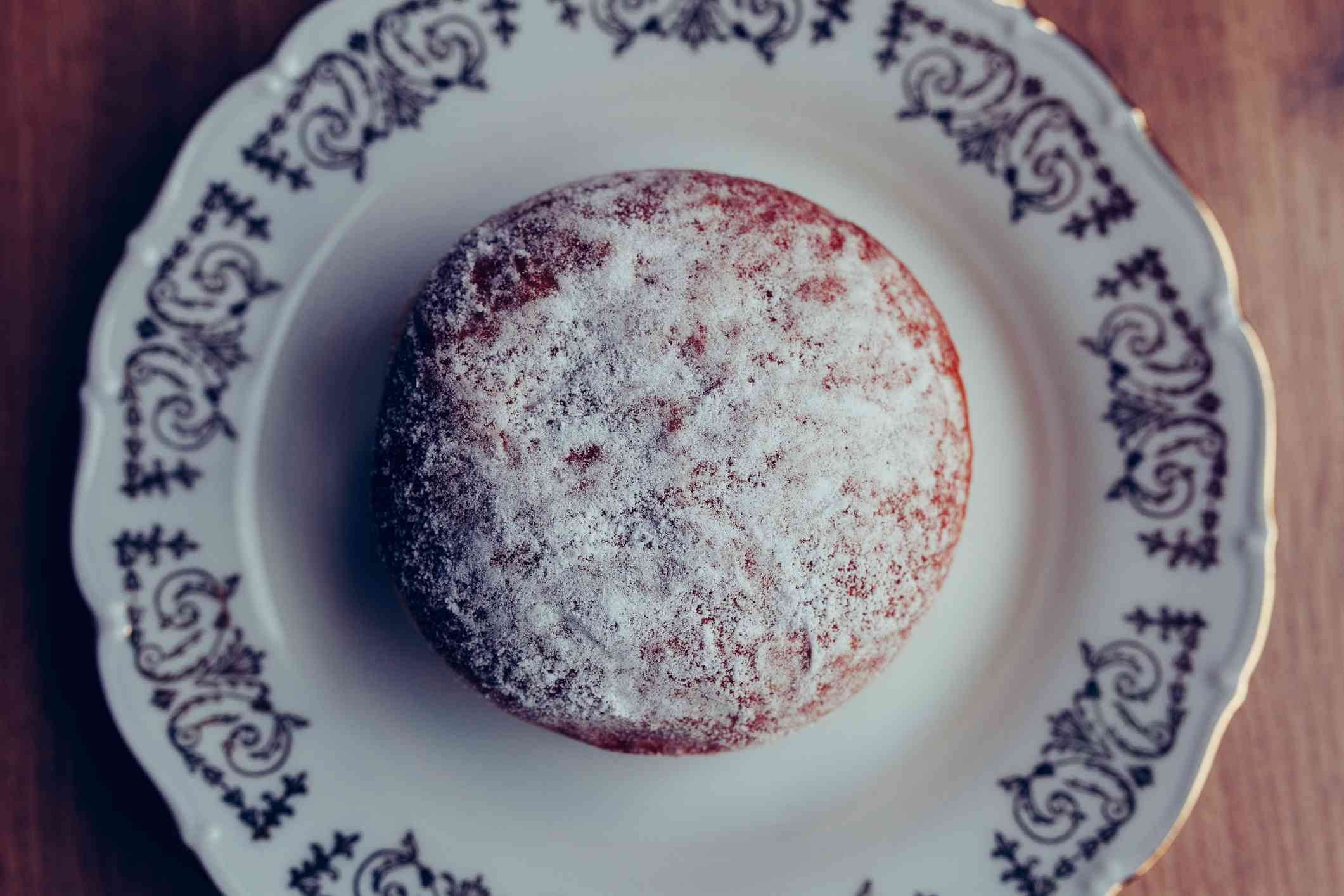 Fresh homemade jelly filled doughnut on a plate, covered in powdered sugar