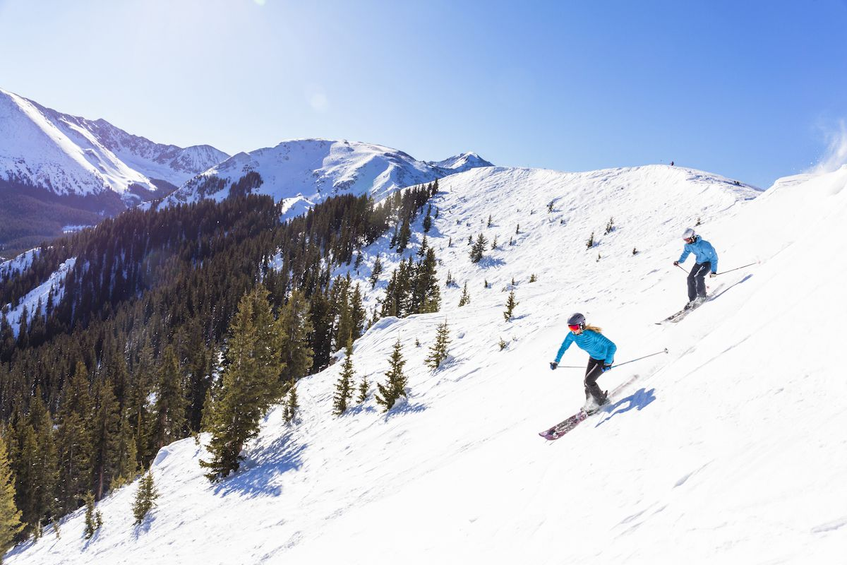 Two skiers start their descent from along a snowy ridge
