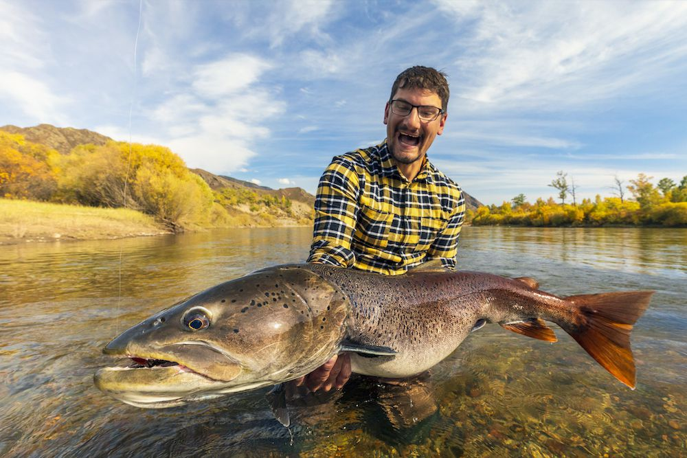A fisherman holds up a massive trout while standing in a river.