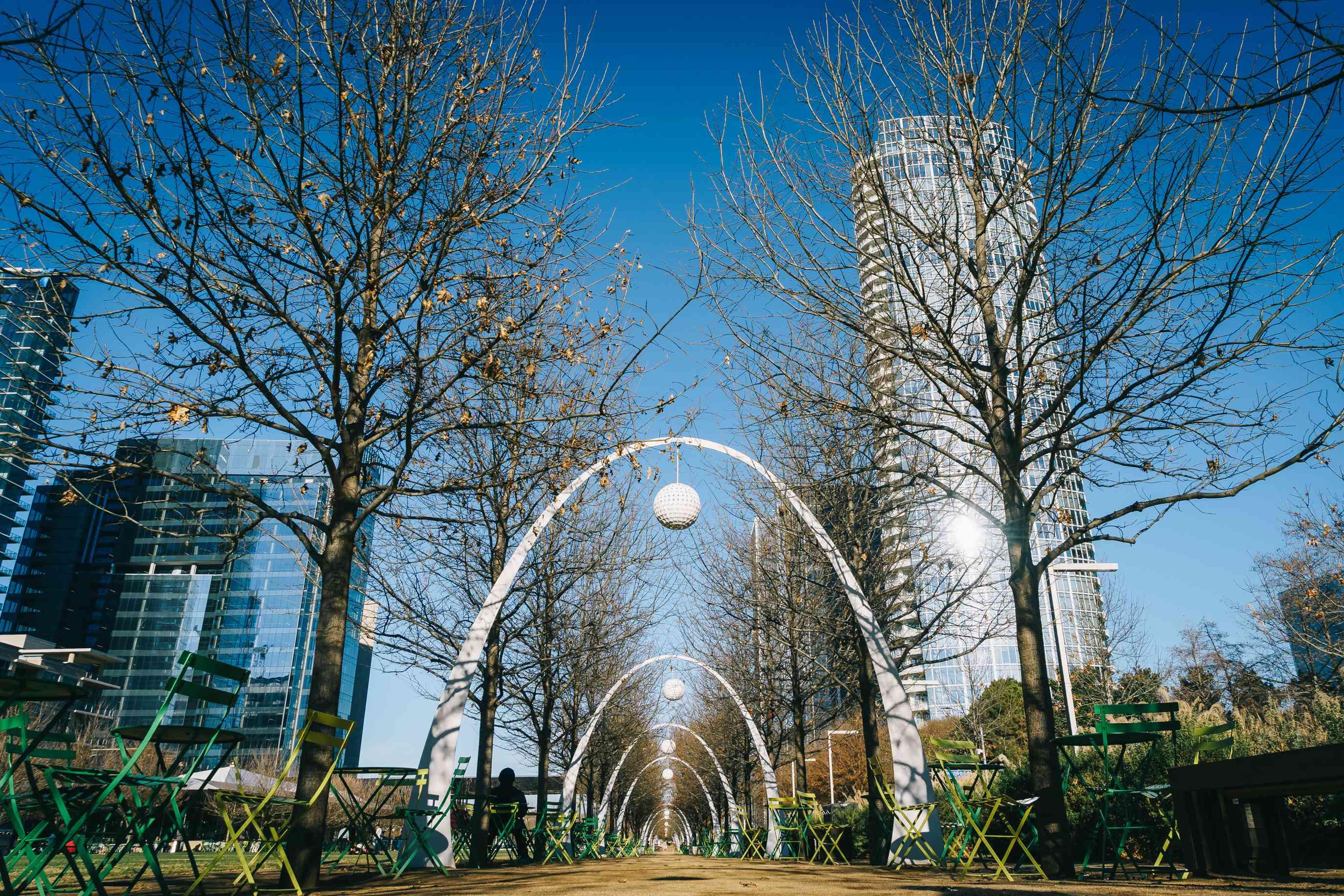 Series of white arches in Klyde Warren Park during autumn