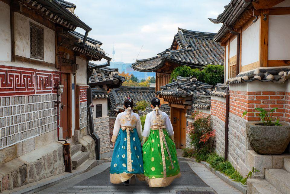 Two woman wearing hanbok walking through Bukchon Hanok Village in Seoul, South Korea