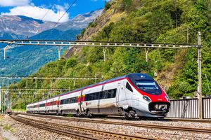 Daytime image of a high-speed train traveling through the mountains from Zurich to Milan
