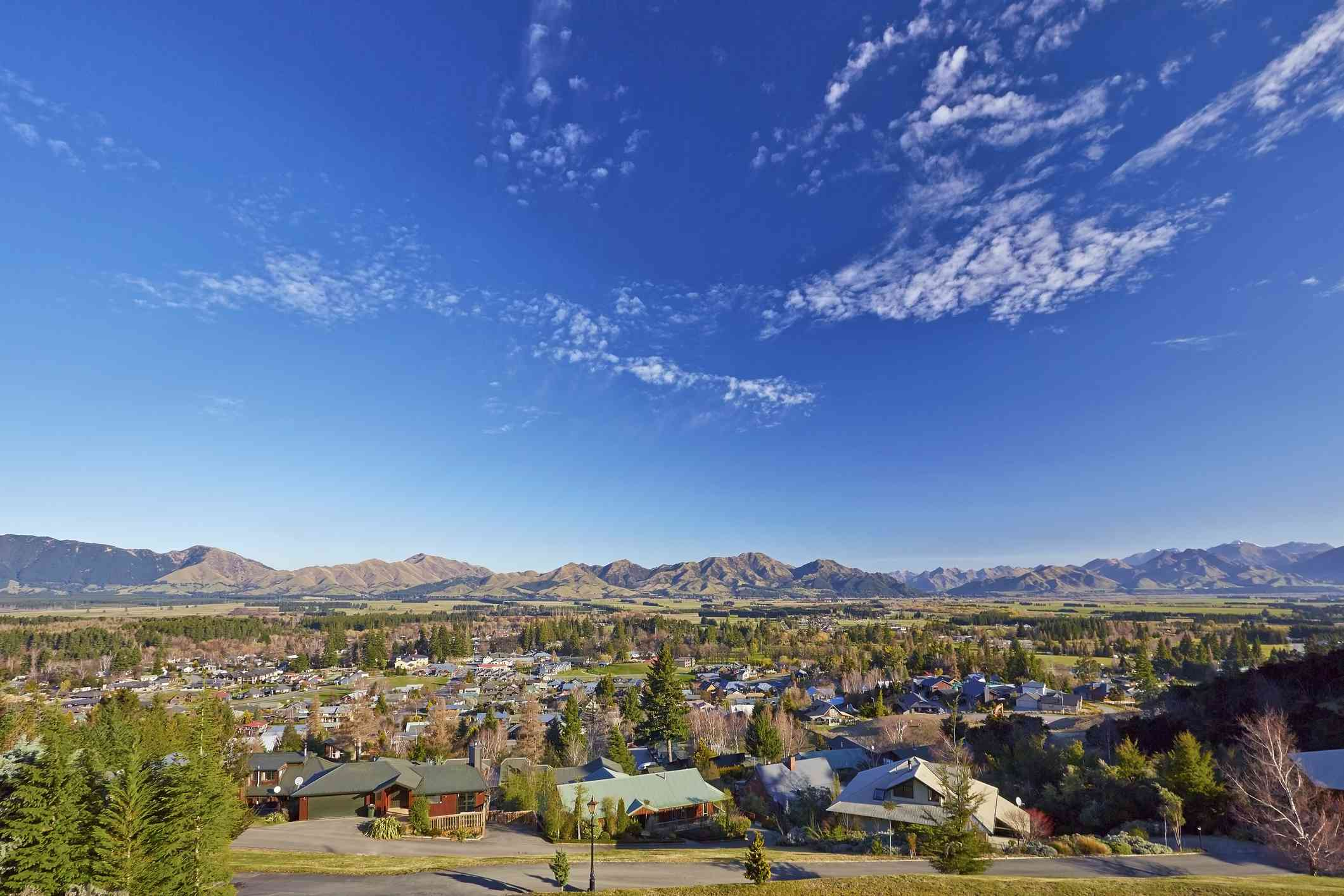 small town with mountains in background and blue sky