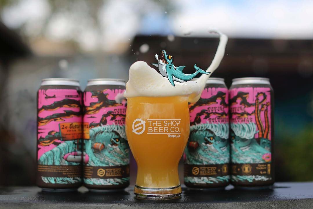 A pint of beer with the foam splashing up and it sits in front of 4 cans of that beer. An animated shark swims on the foam wave