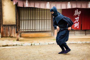 Japanese ninja in black costume stalking in Edo village