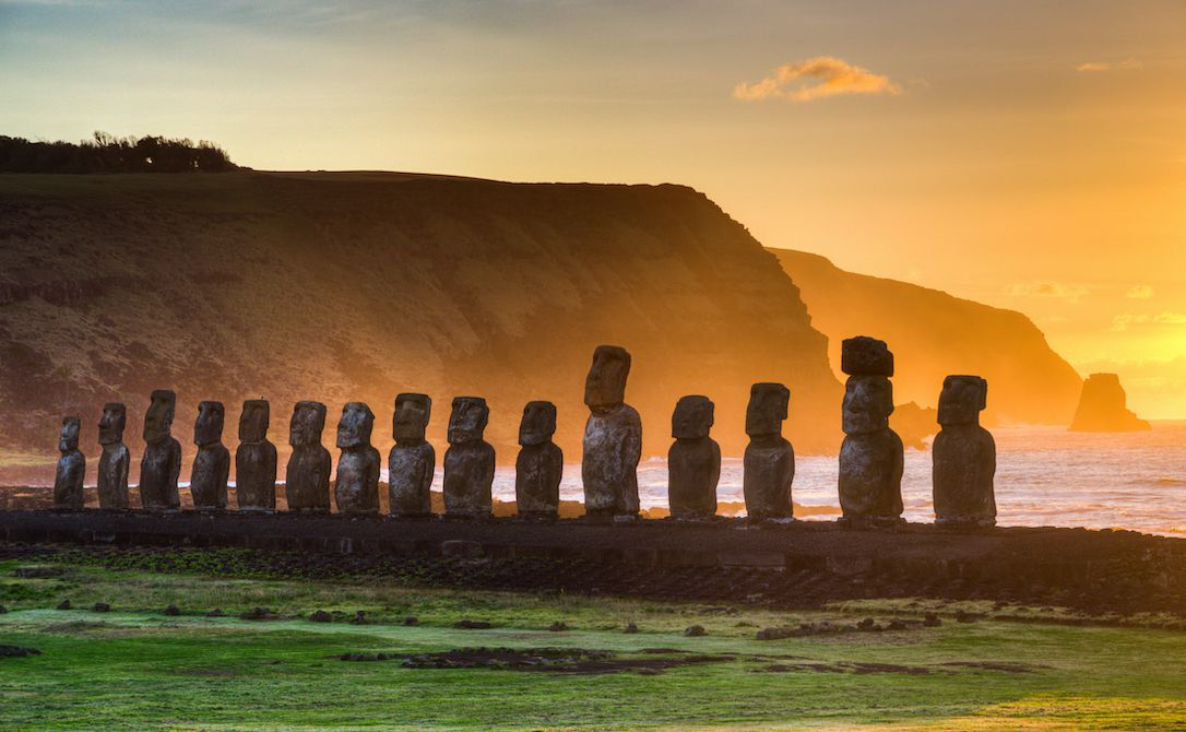 Sunrise on Easter Island with the famous statues in the foreground.