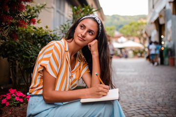 young woman writing in a journal on cobblestone street