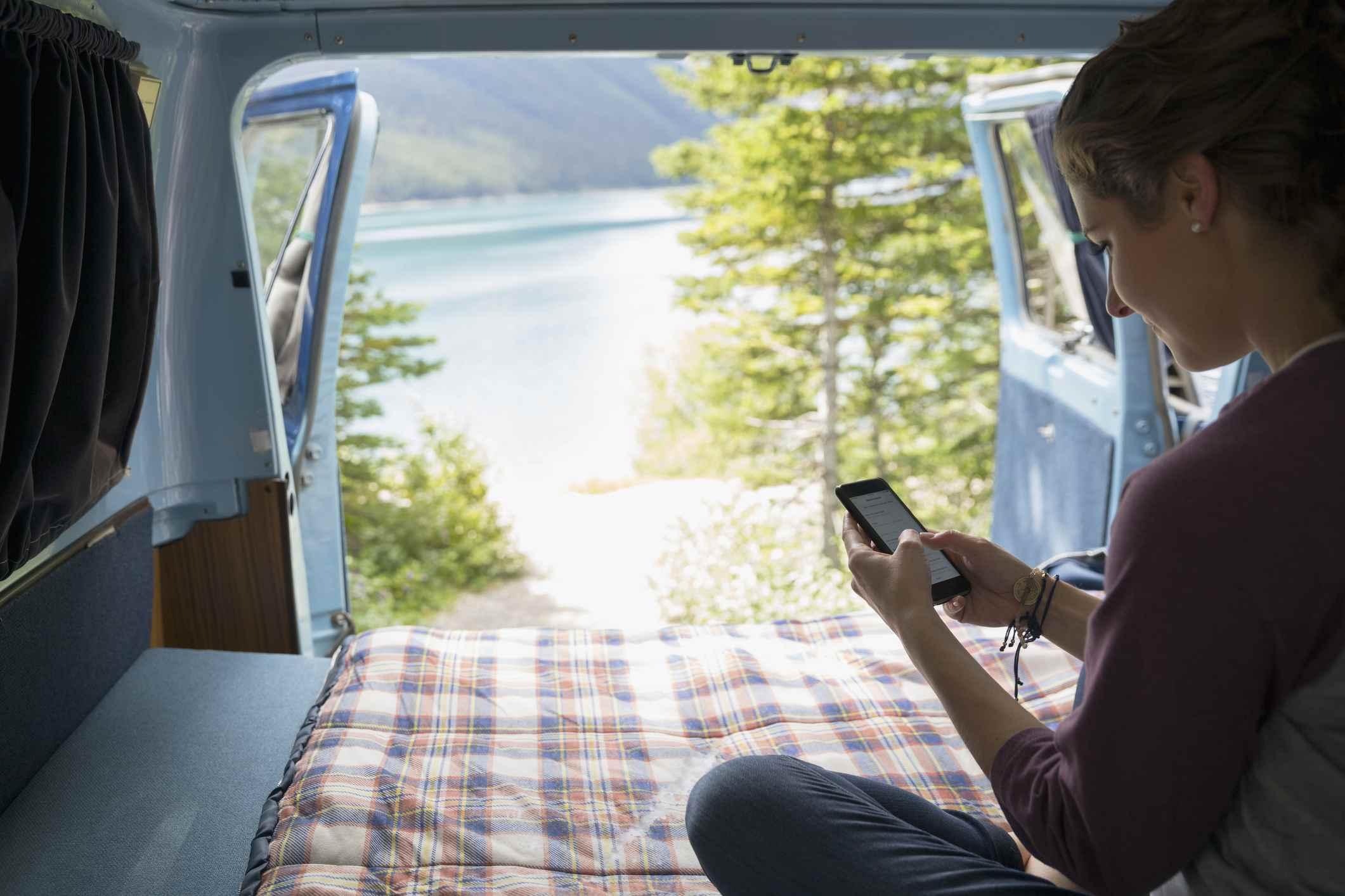 Mujer enviando mensajes de texto con el teléfono celular en la parte trasera de la caravana con vista remota al lago