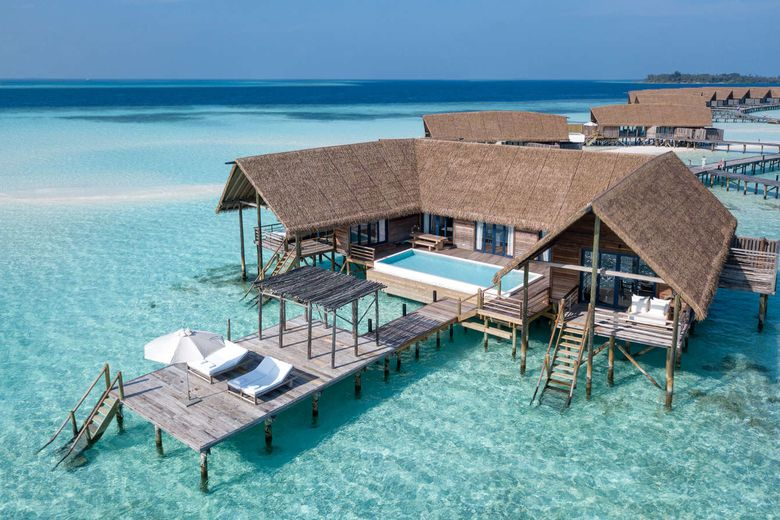 Thatched roof overwater villa in the Maldives with a pool and lounge chairs