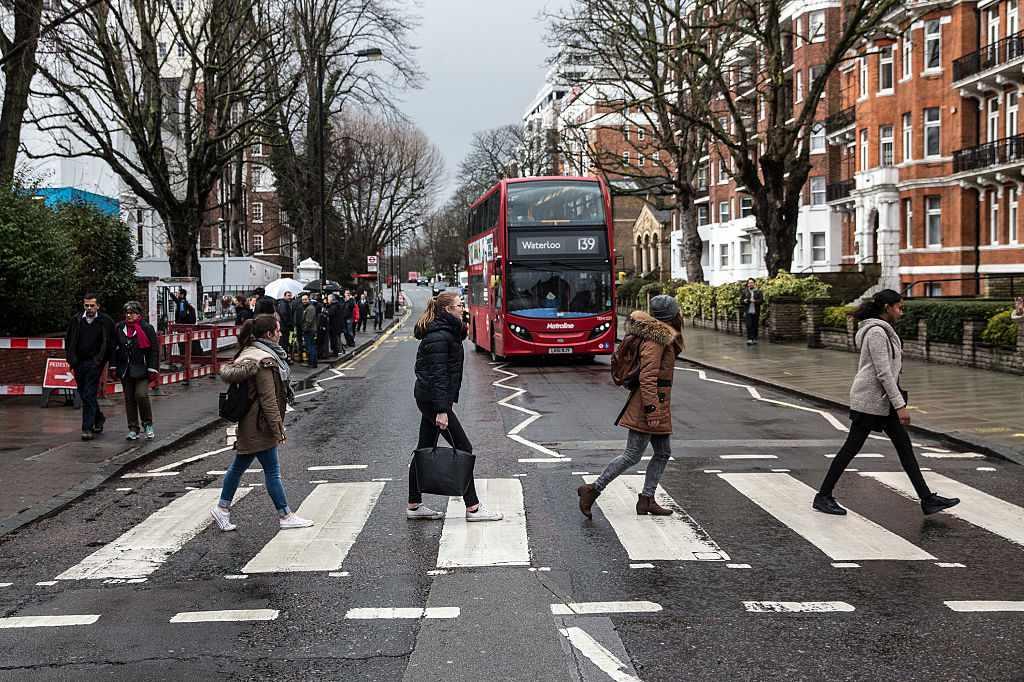Beatles fans walk across the famous Abbey Road zebra crossing in London.